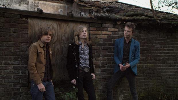 Drei junge Männer vor einer Backsteinmauer auf einem alten Industriegelände