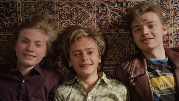 Three Boys lying on a carpet and smiling into the camera