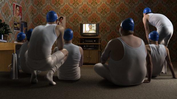 Eine Gruppe Ruderer sitzt vor einem Fernseher auf dem Boden