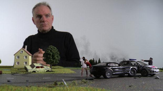Ein Mann beobachtet eine Unfallszene auf dem Tisch einer Trickfilmproduktion