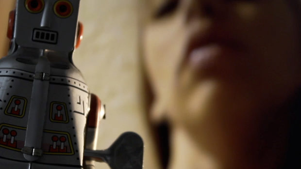 A toy robot crossing in front of the face of a young woman