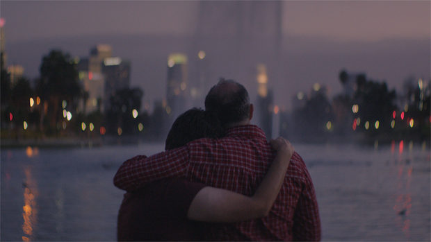 A couple watching a fountain at sunset