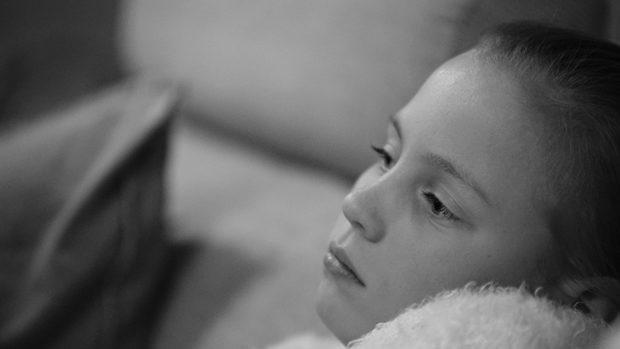 Schwarzweiss-Foto des nachdenklichen Gesichts eines jungen Mädchens im Halbprofil