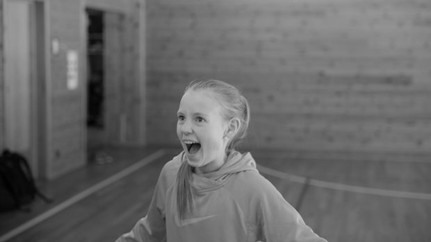 Black and white picture of a laughing girl in a gym