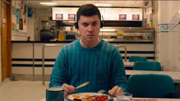 Ein junger Mann mit Kopfhörern beim Essen in einem Restaurant