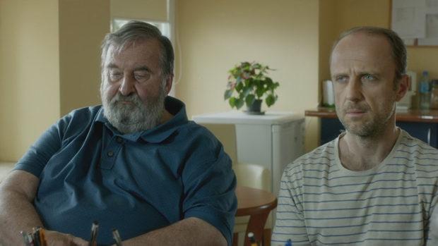 Ein alter und ein junger Mann sitzen nebeneinander in einer Arztpraxis