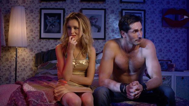 Ein junges Paar mit verzweifelten Gesichtern sitzt auf Rand eines Bettes