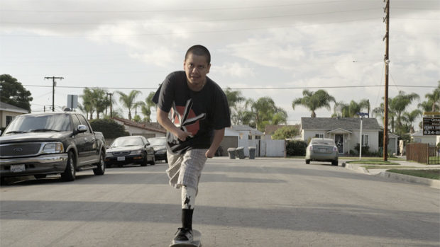 A young Latino skating on a street of his neighbourhood