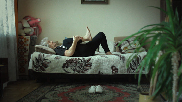 An elderly lady doing gymnastics on her bed