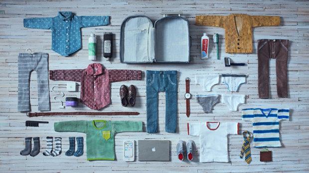 Rund um einen leeren Koffer liegen streng geometrisch geordnete Kleider auf dem Boden