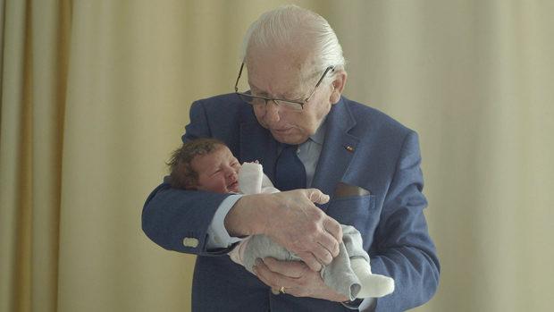 Ein alter Mann wiegt einen Säugling in seinen Armen