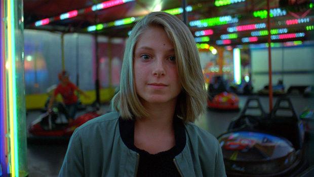 Ein junges Mädchen vor einer Jahrmarktsbahn
