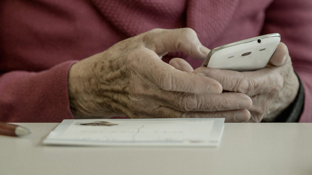 Die Hände eines alten Menschen mit einem Mobiltelefon