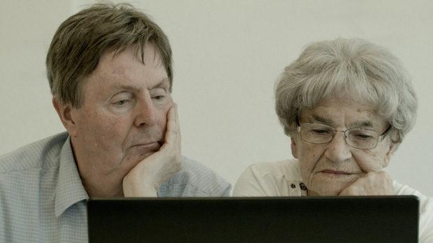 Eine alte Frau und ein alter Mann blicken ratlos auf einen Computerbildschirm