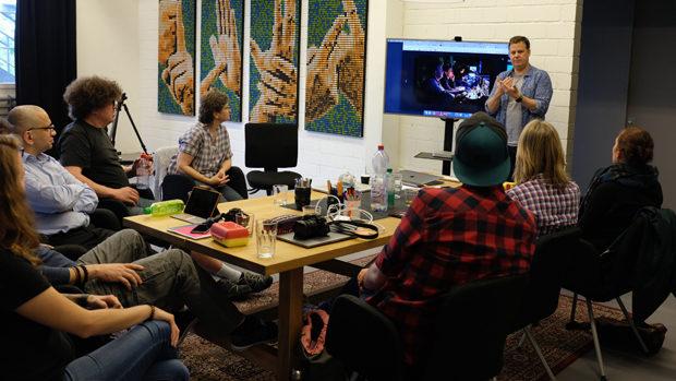 Ein Mann vor einem TV-Bildschirm spricht in einem Seminarraum vor einer Gruppe von sieben jungen Menschen