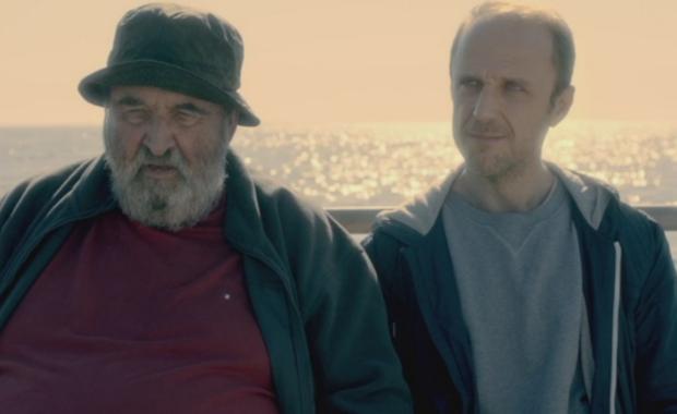 Ein alter und ein junger Mann sitzen an der Reling eines Schiffes, im Hintergrund glitzert das Meer.