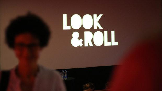 Eine Besucherin im halbdunklen Kino vor der Leinwand mit dem look&roll-Logo