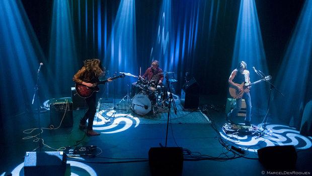 Die drei Musiker auf der Bühne in blauen Scheinwerferkegeln.