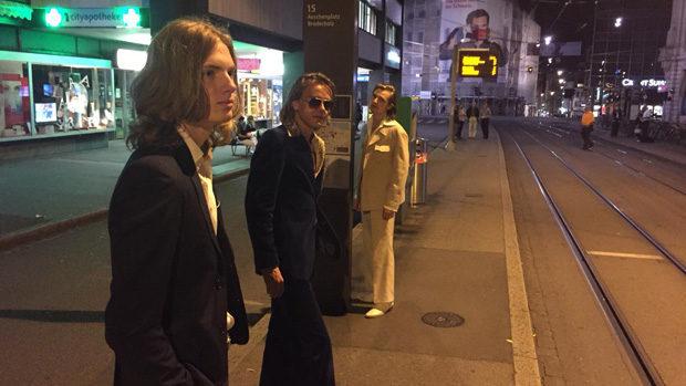 Die drei Musiker in eleganter Kleidung nachts an einer Tramhaltestelle
