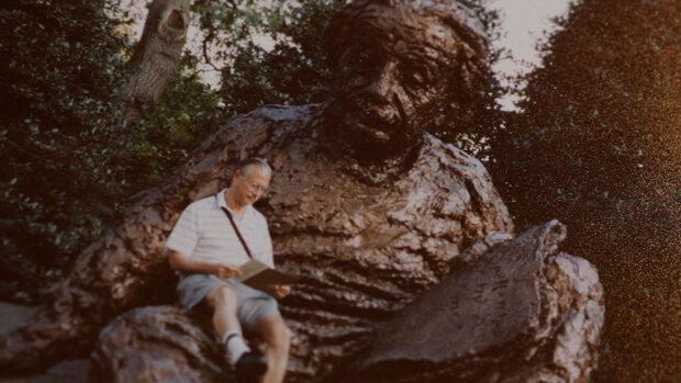 An elderly man reading a book in the lap of an enourmos sculpture of Albert Einstein