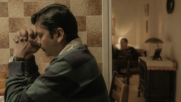 Ein Mann sitzt an einem Tisch und stützt verzweifelt seinen Kopf auf die gefalteten Hände