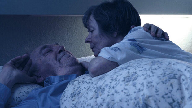 An elderly couple embracing each other in bed