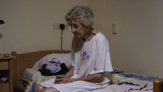 Eine alte Frau im Nachthemd sitzt auf dem Bettrand