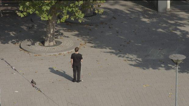 Ein Mann mit Blindenstock steht einsam auf einem grossen Platz und lauscht.
