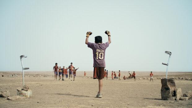 Ein kleiner Junge mit einem Bein jubelt über ein Tor seiner Fussballmannschaft