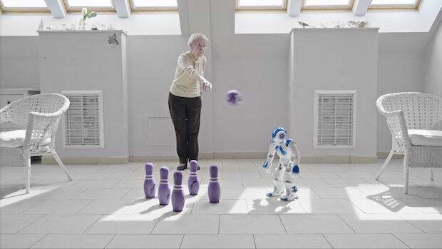 Eine alte Frau kegelt zu den Anweisugen eines kleinen Roboters