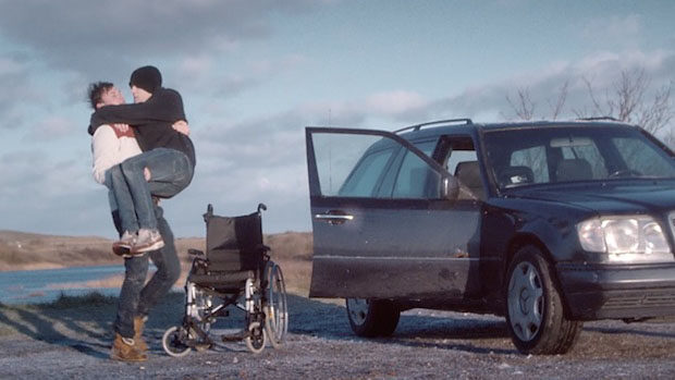 A young man transfer another young man from a wheelchair into a car.