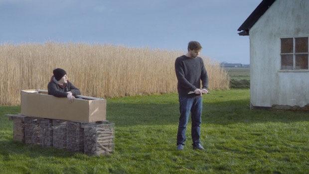 Ein junger Mann sitzt aufrecht im Sarg und lauscht seinem Freund bei einer Rede