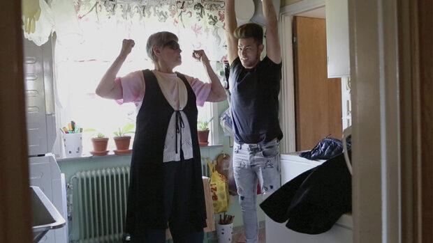 Eine alte Frau weist einen jungen Mann bei der Gymnastik an