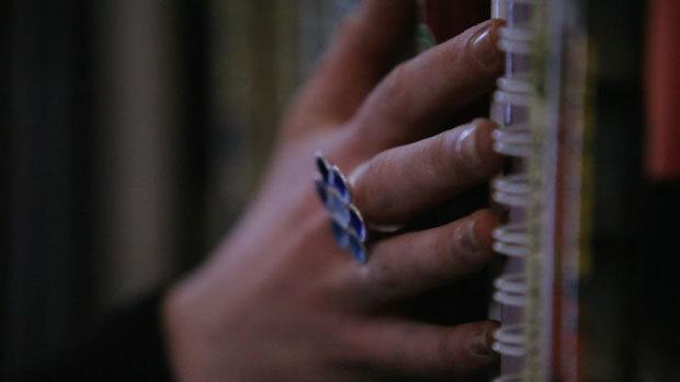 Eine Frauenhand streicht an den Buchrücken eines Regals entlang