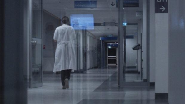 Rückenansicht einer Pflegerin auf einem langen Krankenhausflur