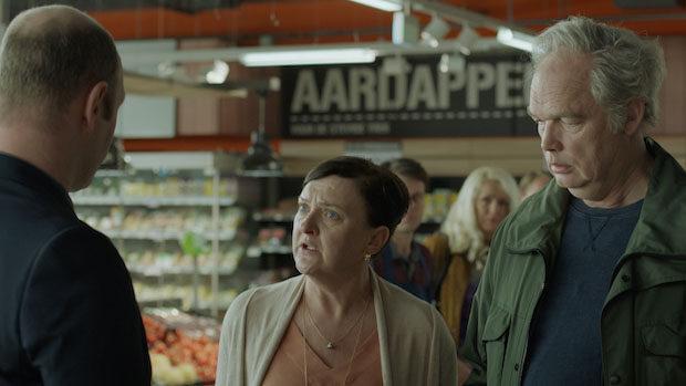 Ein älteres Paar diskutiert in einem Supermarkt mit einem Mann