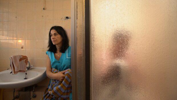 Eine Frau in einer Arbeitsschürze betreut einen alten Mann beim Duschen