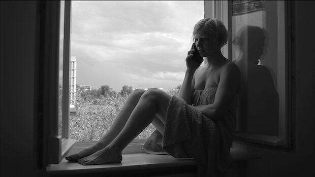 Schwarzweiss-Aufnahme einer jungen Frau, die auf dem Fenstersims sitzend telefoniert