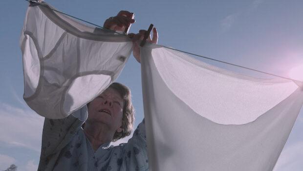 Eine alte Frau hängt bei strahlendem Sonnenschein im garten Herrenunterwäsche auf