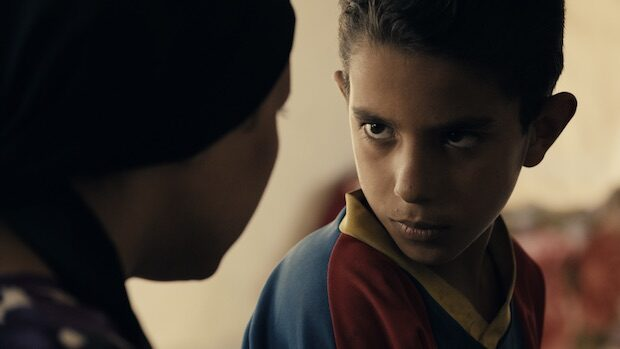 A young syrian boy looking into his mother's eyes