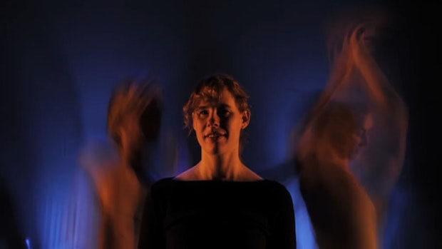 Der Oberkörper einer jungen Frau in einem dunklen Raum