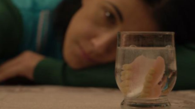 A caretaker pensively watching a set of teeth in a glass of water