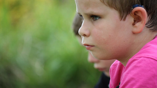 Profile of a pensively looking young boy outdoors
