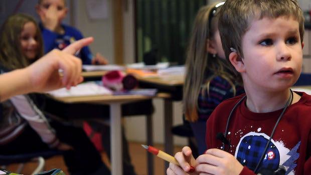 Ein kleiner Junge mit Hörgeräten im Klassenzimmer