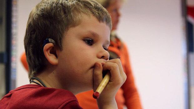 Profilaufnahme eines kleinen Jungen nmit Hörgerät im Klassenzimmer