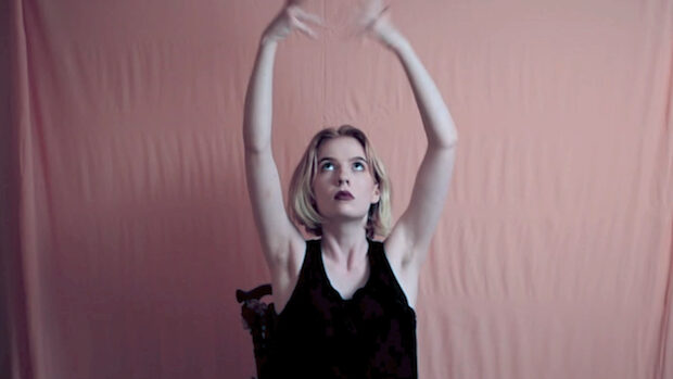 A young blond woman stretching her arms in the air