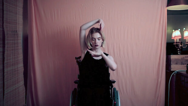 Eine junge schlanke Frau im Rollstuhl umrahmt ihr Gesicht mit den Unterarmen