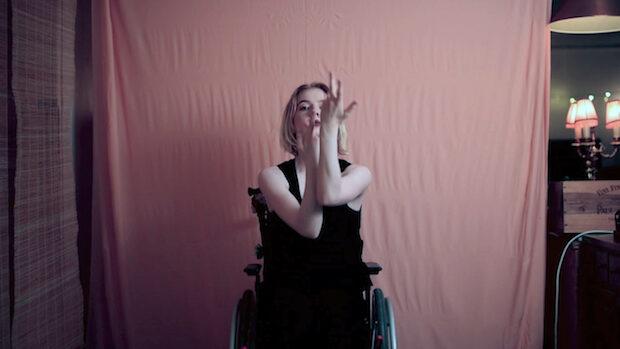 Eine junge Frau im Rollstuhl verschränkt die Unterarme vor ihrem Gesicht