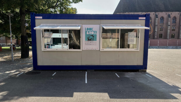 An outdoor container with two counter windows and a festivalposter
